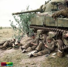 "M4A2, Sherman Mk III ""Cameo"" (T146946) tank crew of 2nd Troop, 'C' Squadron, 13th-18th Royal Hussars, 27th Armoured Brigade rest and write letters home by the side of their vehicle, Normandy, 10 June 1944."