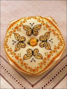 "This pretty pattern features yellow butterflies framed by a green-gray vine with topaz hearts and tangerine rosebuds. The backing design was inspired by a 17th century knot garden. Size: 4 1/2"" diameter x 2"" high. Made with 14-count, but may use 28-count. Skill Level: Easy"
