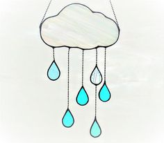 This handmade suncatcher features a whimsical puffy cloud with suspended raindrops. You may select the type of glass (iridescent opaque while or wispy white) and the color of raindrops (blues and greens or rainbow). The Cloud and raindrops measures approximately 14 x 6 at is