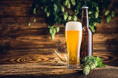 Glass of beer and bottle on old wooden table and wooden backgrou - Glass of beer and bottle on old wooden table and wooden background