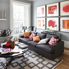 A dramatic wall of red and orange prints in the living room brings colour to this modern monochrome scheme