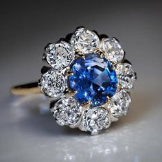 Circa 1910 An antique 18K Gold and Platinum engagement ring is centered with a 2.24 ct natural blue Sapphire surrounded by sparkling bright white old European cut Diamonds (G-H color, VS2-SI1 clarity). Estimated total Diamond weight is 2.40 ct. The Diamonds are set in Platinum over