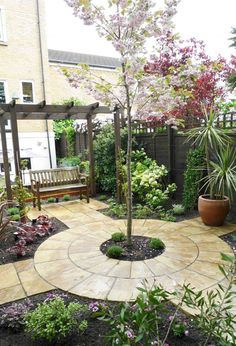 Traditional Court Yard Gardens Ideas With Round Shape Stone Floor also Gravels and Flowers Pot also Green Plants and Wooden Long Chair