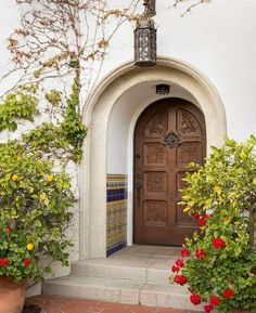 The delightful entry to this 1929 Spanish Colonial-style home is made all the more inviting with potted dwarf orange trees, red carnations, and colorful Spanish tiles leading to a massive carved wooden front door.