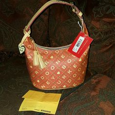 NWT Dooney & Bourke crossword style red Beautiful red crossword style Dooney & Bourke. Never used. One inside zip pocket, two inside pockets cell phone pocket. Key holder. Tassle zip. Registration card included :) please let me know if you have any questions. Dooney & Bourke Bags Hobos