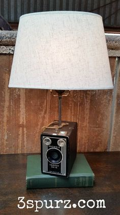 1940's Brownie Target Six-16 camera turned into a lamp. The camera is mounted to a book as the base. Follow us for more wonderful pins at http://pinterest.com/3spurzdandc/ http://facebook.com/ http://www.3spurzdesignsandcollectables.com/home 3 Spurz D&C Repurposed /Refurbished Creations!!