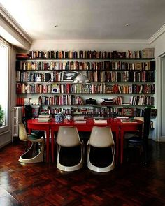 The red table and wall of books can try, but even they can't steal focus from these curvy white dining chairs. via Nuevo Estilo