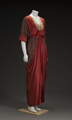 """Dress: ca. 1910's, American, silk satin, silk velvet, lace. """"Between 1908 and 1918 clothing styles gradually changed to reflect the new century and new women. Waistlines were raised, and longer and straighter corsets replaced the S-shaped ones. The corset—almost reaching below the thighs—helped achieve tubular, slimmer silhouettes. These columnar sheath dresses were reminiscent of the fashion of the early 1800s. The hemlines rose in this period to reveal the ankles."""""""