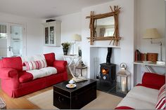 red sofas - black coffee table provides a great counterbalance to the red sofa in an otherwise 'nordic' room.