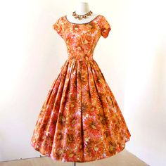 1950s vintage jerry gilden of new york tangerine floral cotton pin-up sun party dress  Jerry Gilden was a maker of moderately-priced women's ready-to-wear in the 1940s into the 1960s. He started his manufacturing business in 1945 and ten years later was one of the top five producers of women's dresses in the United States.  Gilden started work in the garment trade when he was just fourteen. For years he worked as a salesman and product developer at Majestic Specialty Company, a maker of…