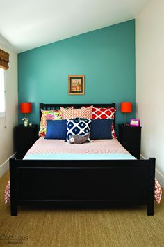 small cottage guest bedroom with lots of bright accents: pillows and accent wall