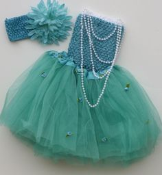 """Adorable Ariel! Sweet aqua/turquoise multi layered tutue dressed up with tiny scattered rosebuds and a satin ribbon at the waist. Shown with double layer crochet top. Of course, the well dressed young princess would never go out without her pearls! Dyed to match crochet headband and 4"""" spikey mum. Fits 1-4 years. Set price $24"""