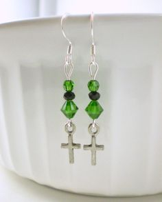 These lovely green cross earrings are made with the high-quality dark moss green (crystal) Swarovski beads, small black glass beads, and pewter cross charms. These earrings make a beautiful green statement with a touch of black to bring out the sweet green color. These come in a cute organza bag ready for gifting.  LENGTH: 1 & 7/8 inches total (ear wire to end of cross charm)