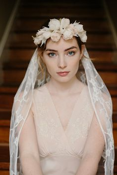 Lush silk roses make up this rich bouquet of floral splendor to crown the bridal tresses, securing a luxurious leaf-patterned French Chantilly lace veil.