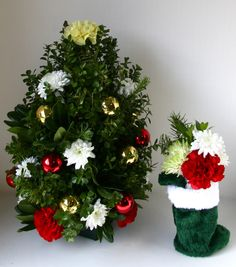 Christmas Flowers. Holiday decorations. Miniature boxwood Xmas tree.  Mini stocking stuffed with flowers. Christmas morning.