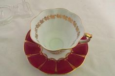 This is a beautiful red and gold vintage tea cup and saucer made by Queen Anne china and made in England. This cup a scalloped cup that is white in the inside with a gold floral design around the top. The outside is red panels with gold edging and a gold type netting design over the
