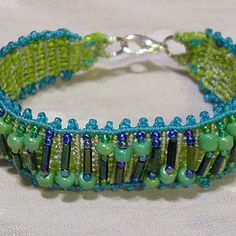 Micro macrame bracelet - hand knotted with nylon beading cord and beaded with a variety of seed and bugle beads in greens and aqua.   Bracelet fits up to 6 1/2 inch wrist (small) and has silver-plated lobster claw clasp.