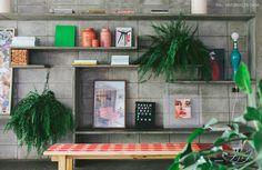 Sala de estar com prateleiras de concreto, muitas samambaias e quadros e objetos.