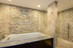HGTV invites you to take a look at this master bathroom with a drop-in bathtub, neutral stone accent wall and nearby walk-in shower.