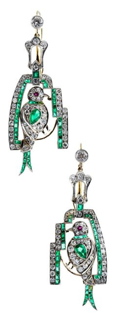 A pair of Art Deco silver, gold, diamond, and emerald earrings, circa 1920.