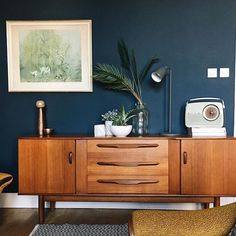 Farrow and Ball Hague Blue walls with a mid century sideboard and Vernon Ward print.