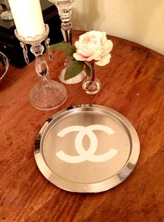 "Silver replica Chanel Tray  12"" Round  This metal tray is great as a candle holder, jewelry ray, catch all for keys, coins, etc. and looks fabulous on a desk! Silver metal with white replica Chanel ""double c"" logo.  12"" square. $50-"