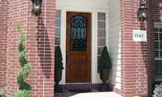 Knotty Alder wood front door with Barcelona wrought iron