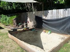 covered sandbox and outdoor play kitchen