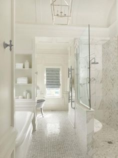 Beautifully designed, well appointed white bathroom with blue accents features a barrel ceiling fixed above a tub nook fitted with a Waterworks Empire Freestanding Rectangular Bathtub with a polished nickel antique tub filler placed on marble basketweave floor tiles between white built-in shelves.