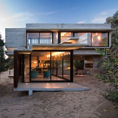 A concrete volume projects from the top of a sand dune to form the upper level of this house in Buenos Aires, on the Argentinian coastline by Luciano Kruk