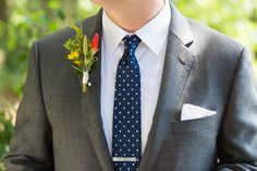 grey suit with navy tie and spring boutonniere for groom