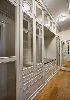 The walk-in closet features stunning and well organized closet cabinets, painted in Benjamin Moore Cumulus Cloud 1550.
