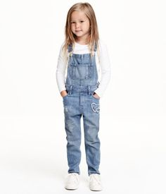 Bib overalls in washed denim with distressed details and adjustable suspenders. Bib pocket, mock fly, and snap fasteners at sides. Side pockets, one with appliqué and back pockets, one with appliqué.