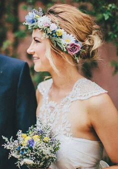 The delicate neck and back of this bride's dress called for a low and loose chignon bun paired with a full floral crown of daises, roses, billy balls and greenery. See the entire wedding here. PC: The Robertsons