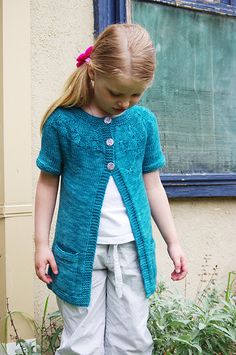 Little Butterflies is a super easy and fun to knit little trans-seasonal cardigan. Knit in dk weight yarn, this little short sleeve cardigan knits up quickly from a circular yoke. It features cute little butterflies flittering randomly around the yoke and perfectly placed pockets. This is a longer line cardigan, that looks equally great worn on its own, or layered.