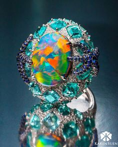 A fiery opal adorned with Paraiba tourmalines, blue sapphires and diamonds from the Colourful collection by Karen Suen Fine Jewellery. Tourmaline Jewelry, Opal Jewelry, Jewelry Rings, Fine Jewelry, Jewellery, Green Opal, Black Opal, Types Of Opals, Beautiful Rocks