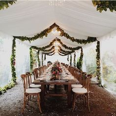 Tented outdoor wedding reception with king harvest table and greenery garland