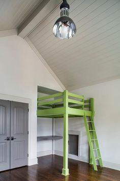 Gray double doors open to a gray and green boy's bedroom features a gray shiplap vaulted cieling adorned with an industrial pendant illuminating a green loft bed with matching ladder.