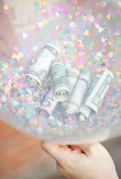 Put Confetti, candy, and money inside a some balloons and tie them together with a big bow!