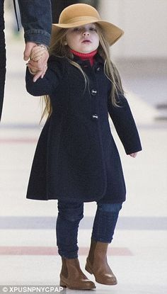 Harper Beckham arrives in New York on Saturday for Fashion Week in a Monnalisa coat, Chloe hat, roll-neck and boots.