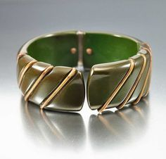 Circa 1930s vintage Deco era spinach green bakelite bangle bracelet with golden brass bands! The bangle has a spring clamper hinged back with the brass bands at an angle giving the whole piece a geome