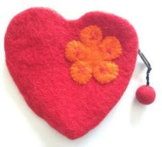 The Reeta Heart purse is made of handmade felt from Artisans in Nepal. It has a single zip (with red pom pom pull) down the side, is lined and has an orange flower.  Dimensions 14cm x 14cm.