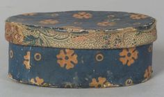 Small Oval Wallpaper Covered Box, America, early 19th century, the box covered in orange floral on blue wallpaper, the rim edge covered with red, blue, and brown printed cotton calico fabrics, (edge wear), ht. 2, dia. 5 1/4 in.