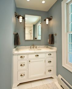 bathrooms - Restoration Hardware Bistro Rectangular Pivot Mirror brushed nickel marine sconces white bathroom cabinet marble countertops blue walls rectangular pivot mirror chocolate brown towels