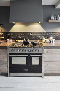 Keuken landelijke stijl gemaakt door RestyleXL. De keuken is gemaakt van steigerhout met een betonnen werkblad. Een groot fornuis, de schouw en krijtbord achterwand geven de keuken een uniek karakter.
