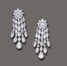 A PAIR OF DIAMOND EAR PENDANTS   Each pear-shaped diamond surmount, enhanced by a marquise and circular-cut diamond surround, suspending five similarly-set articulated tassels, the central tassel terminating in a pear-shaped diamond, mounted in white gold