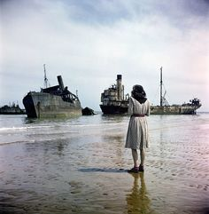 A woman looks out at ruined ships used in the D-Day storming of Normandy. Photograph by David Seymour, 1947