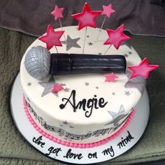 Mic drop! So cool to have a microphone on top of a cake, perfect for a girl's birthday cake with pink stars and music notes along the side of the cake.