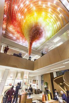 artiste contemporain sud coréen Do Ho Suh à l'occasion de l'ouverture d'une nouvelle boutique Louis Vuitton dans le quartier de Shinjuku à Tokyo, il a réalisé un chandelier étonnant. Effectivement cette sculpture monumentale habille non seulement le plafond du magasin mais diffuse également une lumière chaude aux couleurs de la marque. L'oeuvre d'art intitulée Cause and Effect, est composée de 42 000 figurines en résine acrylique