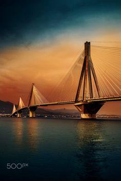 Ponte Rio–Antirrio ou Ponte Charilaos Trikoupis, ponte rodoviária na Grécia sobre o Estreito de Rio-Antirrio que está entre o Golfo de Patras e o Golfo de Corinto. Inaugurada em 2004, liga o Antirrio no Peloponeso, ao Rio na Grécia continental. A ponte estaiada tem 2 vias em cada sentido, uma faixa de emergência e uma para pedestres. Tem um total de 2.883 m de comprimento, 2.252 m sobre o mar, rampa de 392 m para acesso ao Rio e outra de 239 m em Antirrio.  Fotografia: David Stojanovic no…